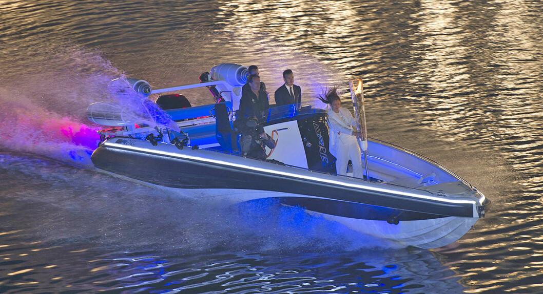 KONSENTRERT: På bildet er David Beckham på vei opp Themsen i den spesielle farkosten Bladerunner BR RIB 35. Fakkel-assistenten passer på den olympiske ild mens Beckham kjører båt. FOTO: AOP/Paul Grover-Rex Features